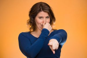 Woman pinches nose pointing at you with finger, you stink